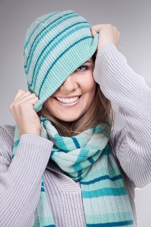 smiling funny girl pulling her winter hat photo