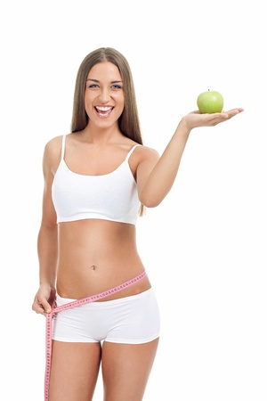 slim and fit woman  in underwear with measuring tape and apple, isolated on white background photo