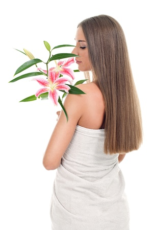 pretty woman in wrapped towel smelling pink lily in hand, isolated on white background photo