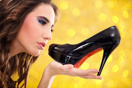 shoes woman: Sensual young woman holding black high heels