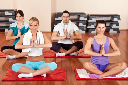 Group of young people doing yoga exercises photo