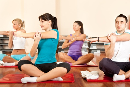group of young people in gym stretching arms photo