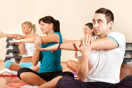 Group of gym people stretching at a gym photo
