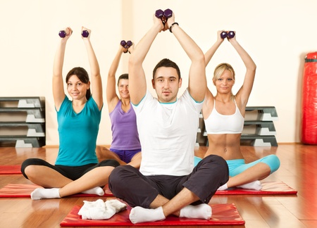 gym girl: young people sitting on mats and doing exercises with dumbbell