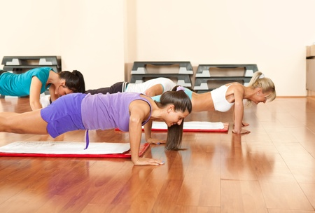 push: young people in gym exercising,  doing push-ups