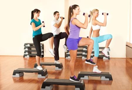 ejercicio aer�bico: Grupo de personas en el gimnasio haciendo ejercicios con pesas libres Foto de archivo