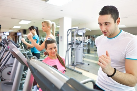 personal female trainer instructing man on treadmill at gym photo