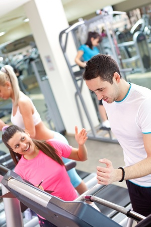 personal trainer encouraging man using treadmill at gym photo