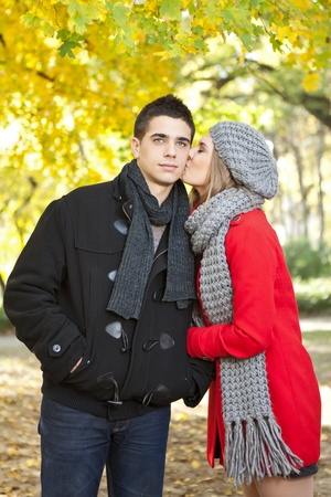 young girlfriend kissing her boyfriend in autumn park photo