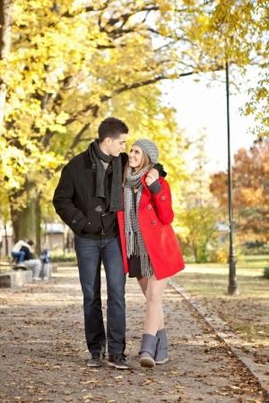 parejas caminando: Pareja feliz en un paseo por el parque, mirando uno al otro