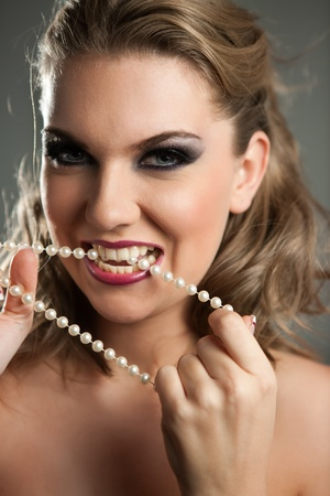 young woman biting her pearls necklace photo