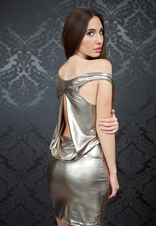 young woman in sexy , silver dress with bare back photo