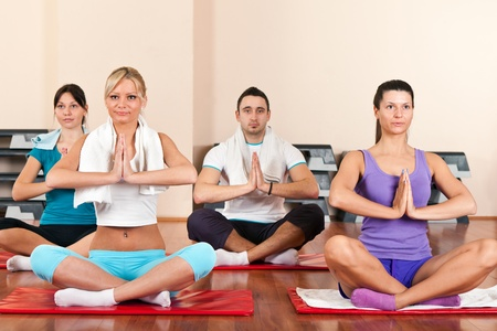 pilates man:  group of young people  sitting cross-legged on mat and meditating