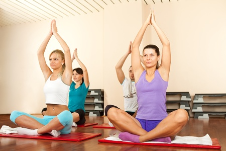 Group of people doing yoga on gymnastics mats Stock Photo