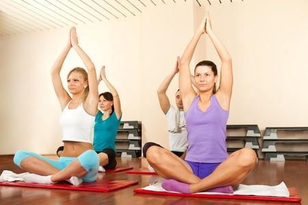 yoga class: Group of people doing yoga on gymnastics mats Stock Photo