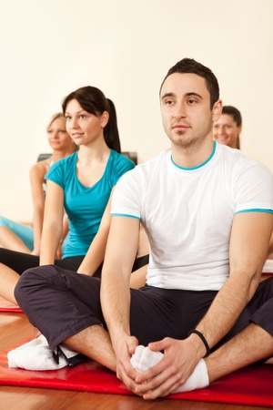 gymnastics girl:  group of people at the gym smiling an doing stretching exercises