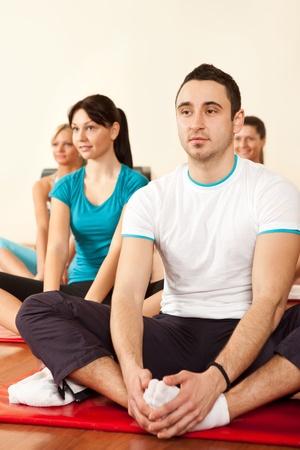 gimnasia: grupo de personas en el gimnasio haciendo ejercicios sonriendo un estiramiento