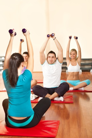 group of young people exercising with dumbbells in fitness club photo