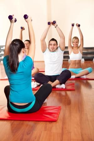 istruzione: gruppo di fitness esercizio con manubri e guardando in istruttore Archivio Fotografico