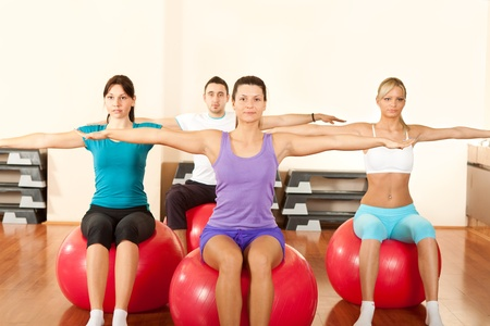 group of people doing  exercises on fitness ball in gym photo