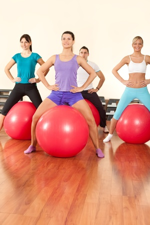 fitness group doing exercises for legs  with fitness ball photo