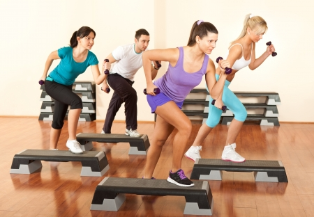 cardio fitness:  group of people exercising with dumbbells in the fitness club Stock Photo