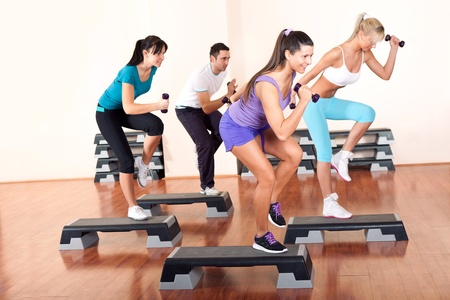 step fitness:  young people stepping with dumbbells in gym