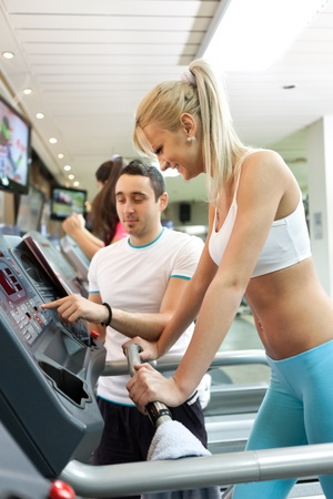fitness trainer instructing girl for setting treadmill photo