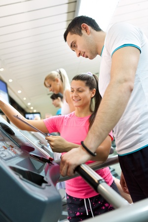 young man walking on a treadmill with his personal trainer photo
