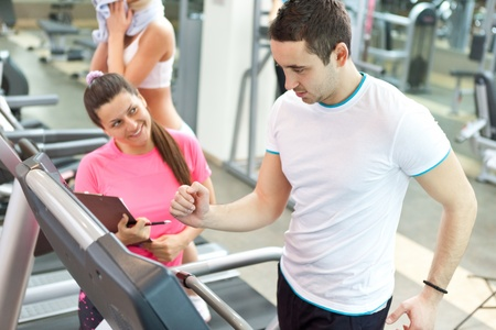 handsome man running on  treadmill  with personal trainer Stock Photo
