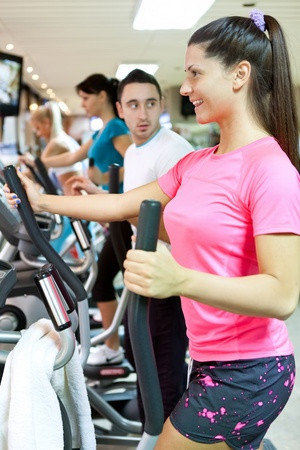 smiling young woman doing cardio workout in gym photo