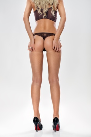 nude ass:  perfect buttocks of elegant  woman in  sexy lingerie on  grey background. Stock Photo