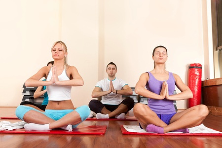 Young people practice yoga in the fitness club photo