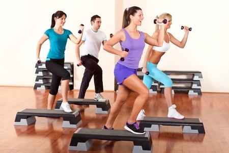 gimnasia aerobica: las personas con pesas en los tableros de paso en el gimnasio Foto de archivo