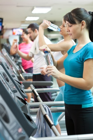 attractive young woman holding a bottle of water at the gym, needed refreshment photo