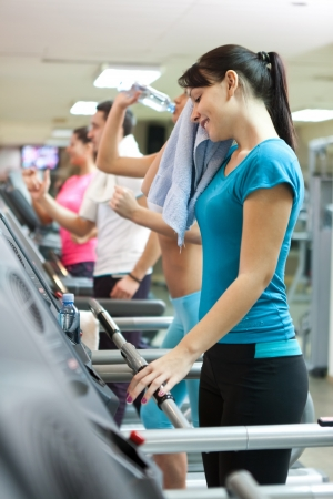 young smiling woman with towel on treadmill, after intensive training  photo