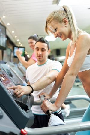 personal trainer instructing woman  how to use treadmill photo