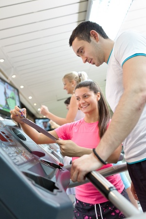 handsome man running on  treadmill , personal trainer compare result of training  photo