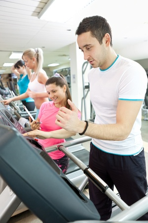 man using treadmill with personal trainer at gym photo