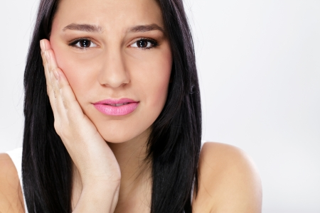 Young woman in pain is having toothache photo