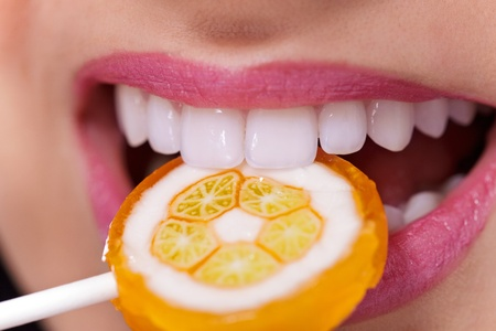 Close up of mouth with perfect teeth and lollipop photo