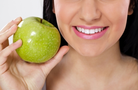 portrait of smiling woman with perfect teeth eating green apple photo