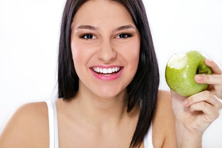 Happy young woman holding green apple with missing bite photo