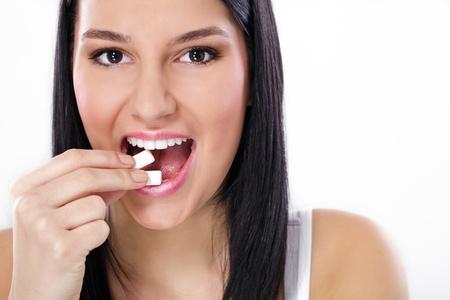 goma de mascar: Joven mujer encantadora sonrisa pone en la goma de mascar la boca, de cerca