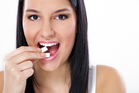 Young charming smiling woman puts in mouth chewing gum, close up photo