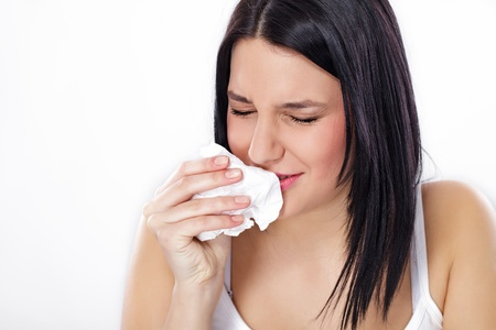 Young woman sneezing, flu or allergy symptoms photo