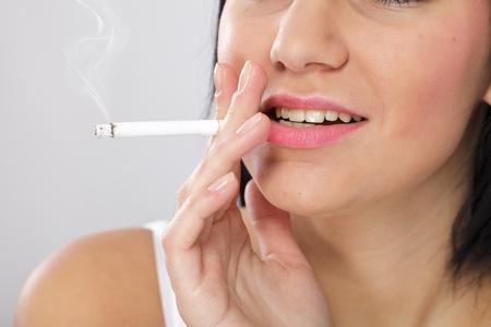 dientes sucios: Primer plano de una mujer joven con la piel mal y los dientes amarillos, fumando un cigarrillo