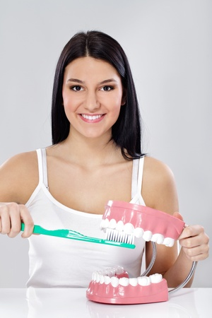 Young girl showing right way to brushing  your teeth with big toothbrush and jaws photo