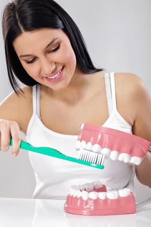 Joven mujer sonriente cepillarse los dientes en las mandíbulas de modelos de plástico