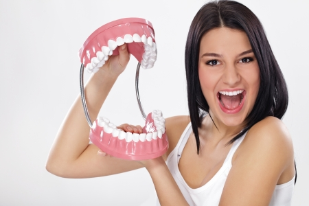 jaw:  Funny woman holding open jaws, showing healthy teeth Stock Photo